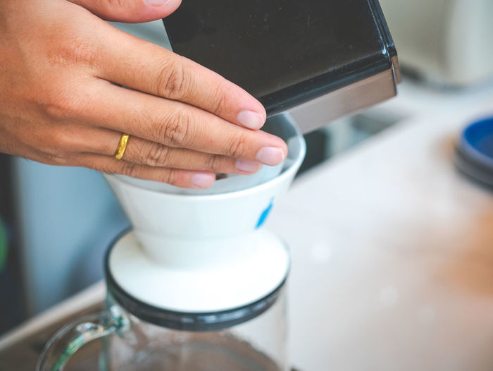 Cropped hands of woman preparing coffee on table in cafe