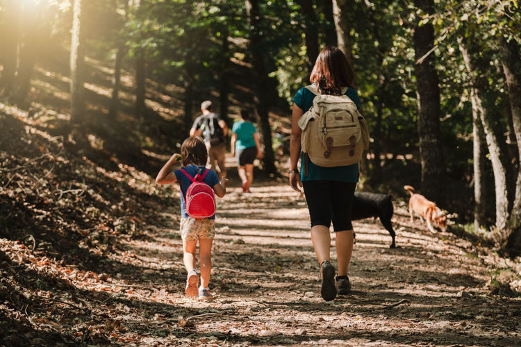 Mother and daughter with dogs hiking in forest