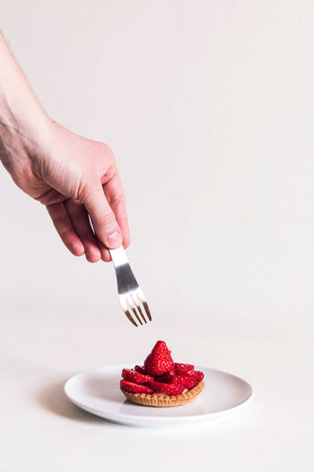 Cropped hand of person holding fork over tart over white background