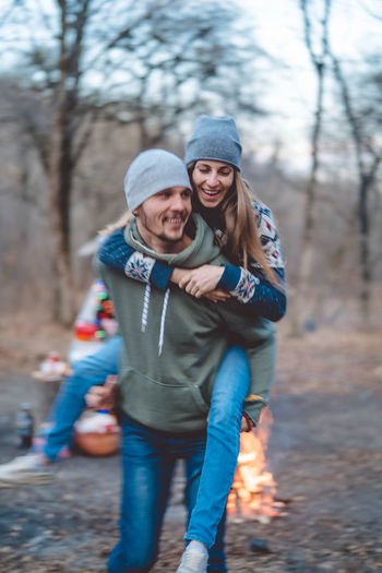 Man carrying girlfriend in forest