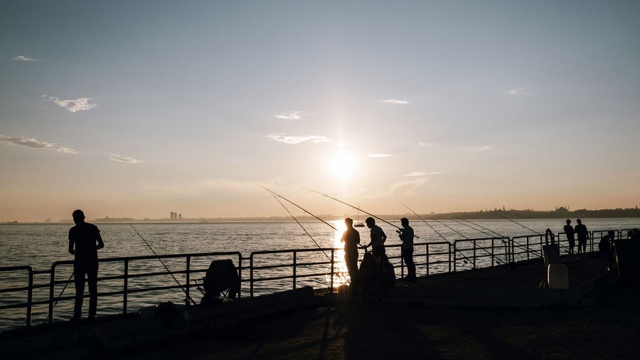 Sky Water Sunset Sea Real People Beauty In Nature Scenics - Nature Silhouette Lifestyles Horizon Over Water Horizon Railing Leisure Activity Beach Nature Land Group Of People Sun Men Outdoors The Great Outdoors - 2019 EyeEm Awards