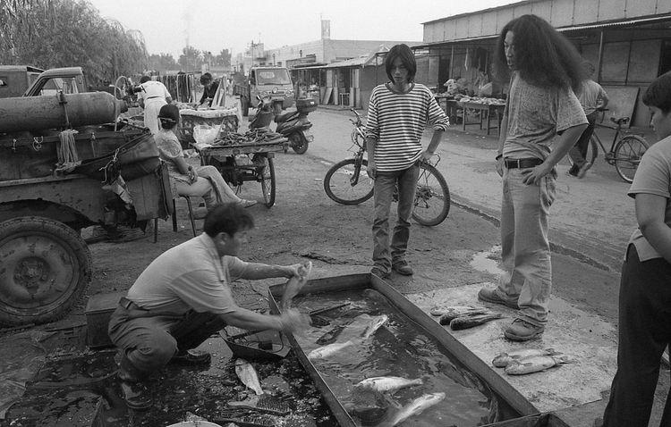 宋庄菜市场是采购主要生活物资的唯一去处,当时做生意的人还不是很多。主要是入住的艺术家还不多,从事其他职业的人群更少。在市场上做生意的有不少都是当地人。如今这个市场上每天的人是乌泱泱、呼啦啦,俨然已是外地人的天下了。图为艺术家在菜场买鱼。2004年 10909308 5093 1613 12820764