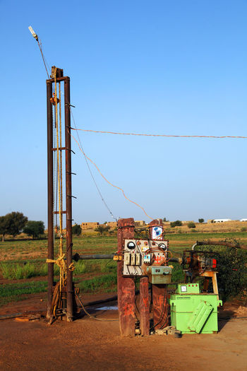 Water Drilling Machine By Grassy Field Against Clear Blue Sky