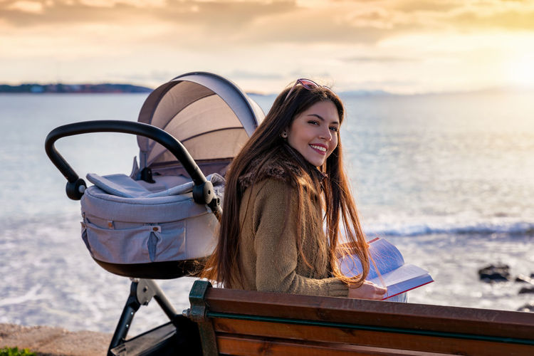 Young mother with her baby sits by the sea and reads a book during sunset time Water Leisure Activity One Person Portrait Sea Looking At Camera Sitting Beach Smiling Lifestyles Young Women Outdoors Nature Mother Baby Book Reading Pram Stroller Pushchair Newborn Mediterranean  Bench Relaxing Togetherness