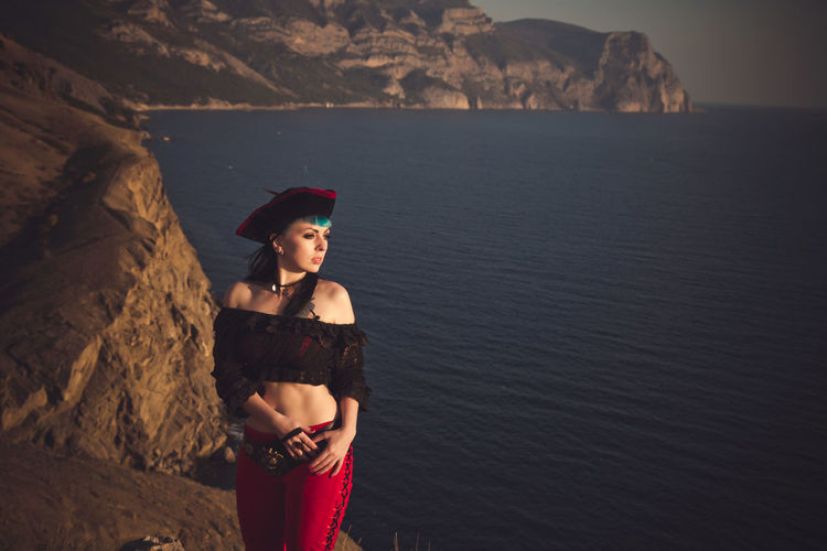 Portrait of a pirate woman at the beach. in anticipation of a pirate ship, sunset