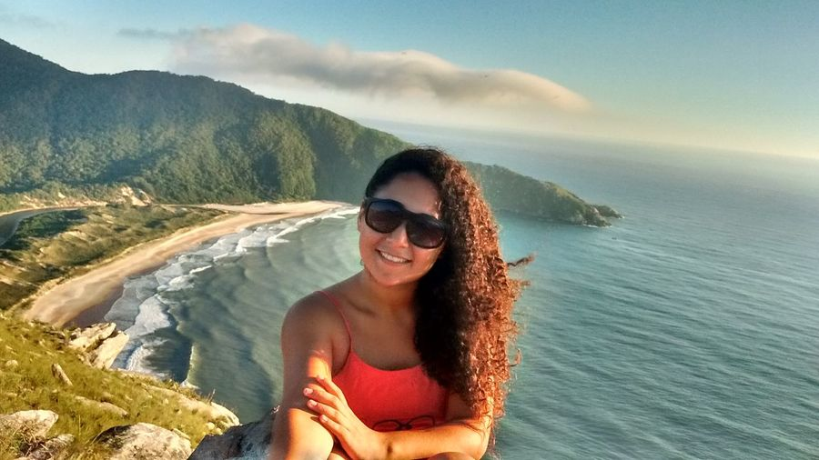 Smiling woman on cliff against sea by mountain at island