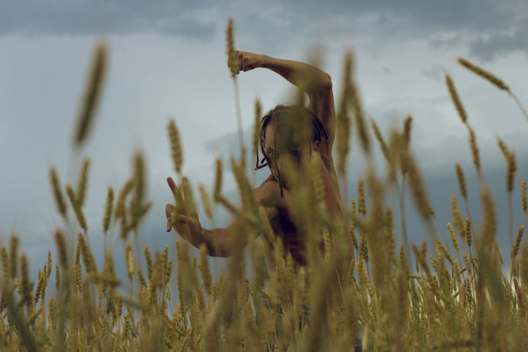 Shirtless young man gesturing while standing at farm