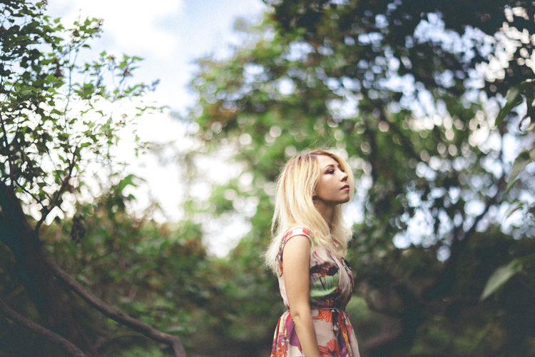 Beautiful Woman Blond Hair Casual Clothing Focus On Foreground Forest Leisure Activity Lifestyles Low Angle View One Person Park People Real People Standing Tree Trees Young Adult Young Women