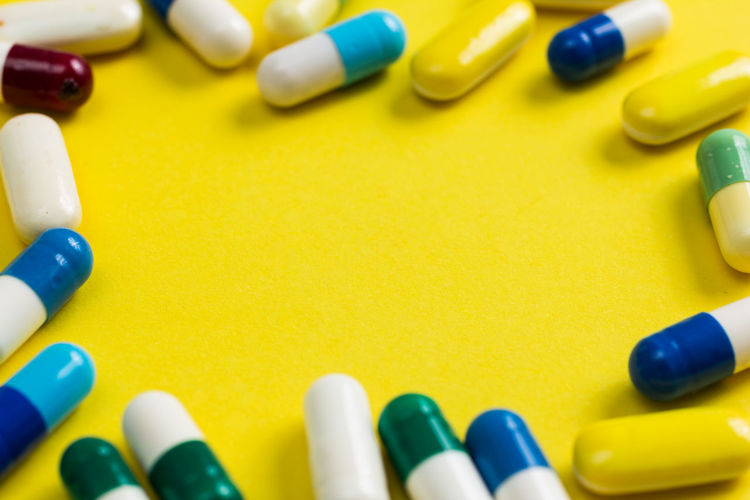 High angle view of medicines on yellow background