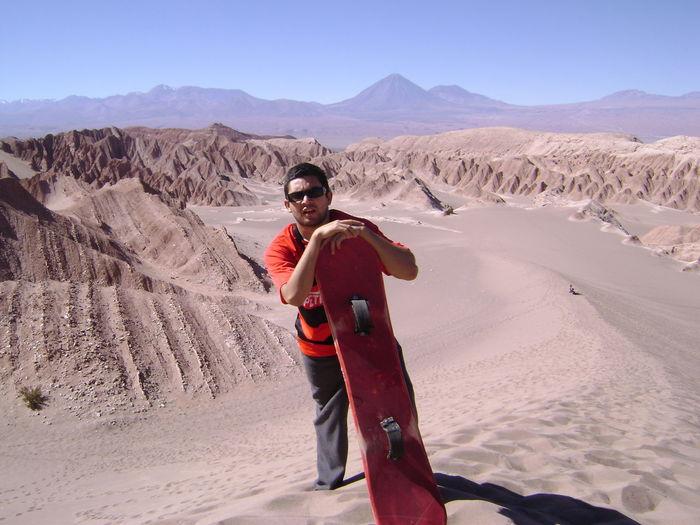 Portrait of man with sandboard standing on desert
