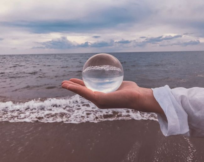 Cropped hand of young woman holding crystal ball over sea against cloudy sky during sunset