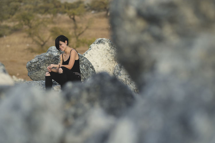 Beautiful young woman wearing black clothes and short haircut sitting on the rocks brunette girl smiling happy in the countryside. Activity Adult Casual Clothing Day Front View Full Length Holding Leisure Activity Lifestyles Nature One Person Outdoors Real People Rock Rock - Object Selective Focus Sitting Solid Young Adult