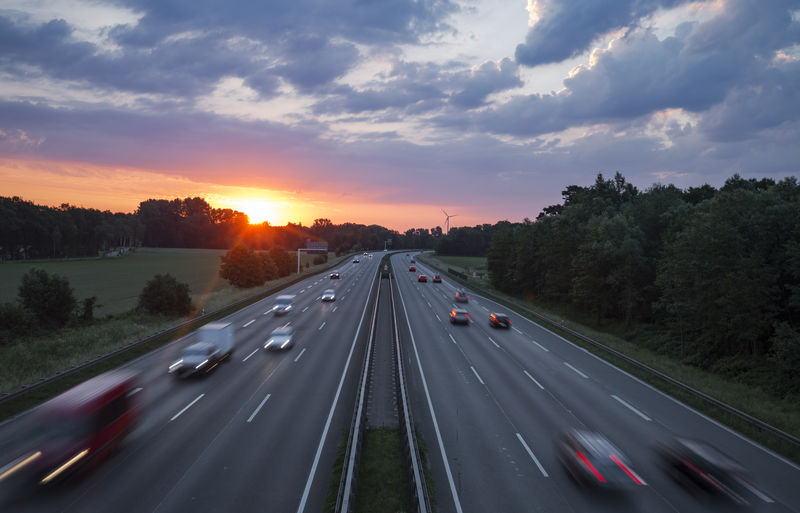 Cars moving on road against sky during sunset