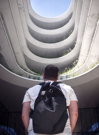 Rear view of man standing against modern building