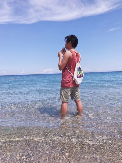 Man Having Drink While Standing In Sea Against Blue Sky
