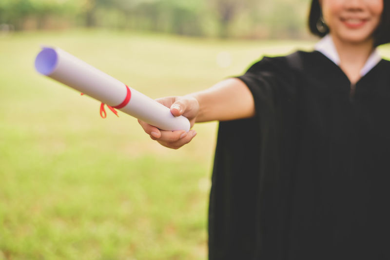 Midsection of young woman in graduation gown holding certificate while standing at park