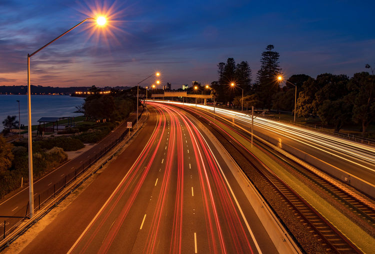 Light trails at Sunset over freeway Perth Australia Architecture Blurred Motion Building Exterior City Cloud - Sky Diminishing Perspective Glowing High Angle View Illuminated Light Trail Lighting Equipment Long Exposure Motion Nature No People Outdoors Road Sky Speed Street Street Light Sunset Transportation