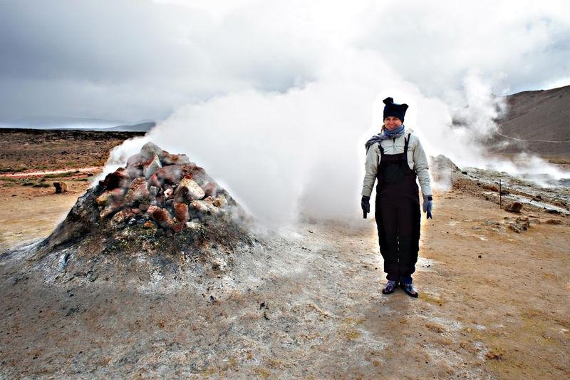 Woman traveling in hverir geothermal area in iceland volcano steaming fumaroles,  alternative energy