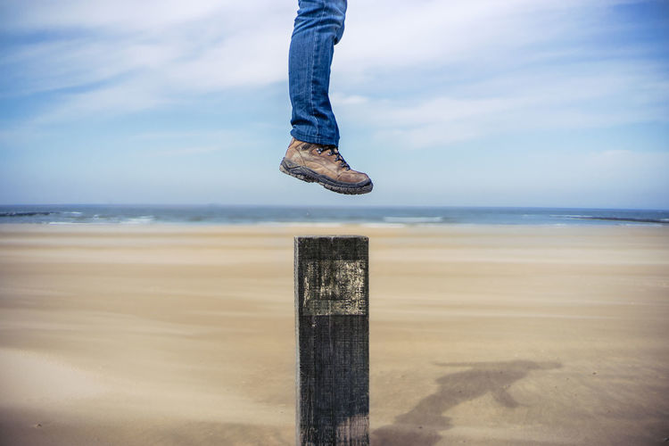 Low section of man in jumping over wooden post at beach