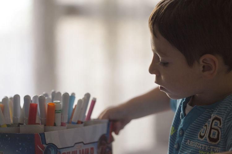Close-up of boy looking at felt tip pens