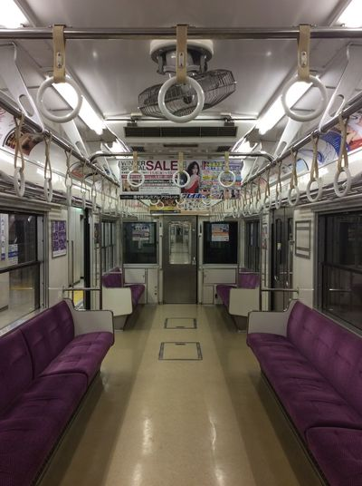 Tokyo Japan The 17.11 To Narita Public Transportation Purple Seating hand rails Rings Advertising Hung From Ceiling Train Door Carriage
