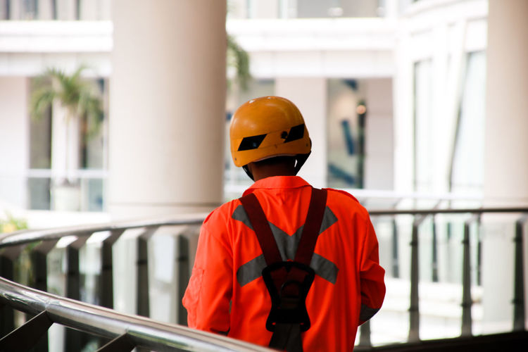 Rear View Of Manual Worker Wearing Workwear Standing By Railing