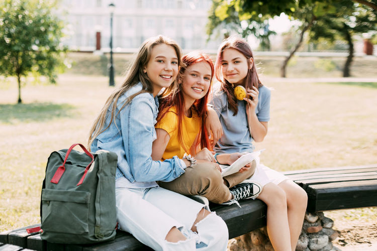 Three schoolgirls are sitting on a park bench, talking, preparing together with the lesson.