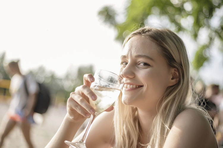 Portrait of smiling young woman having wine
