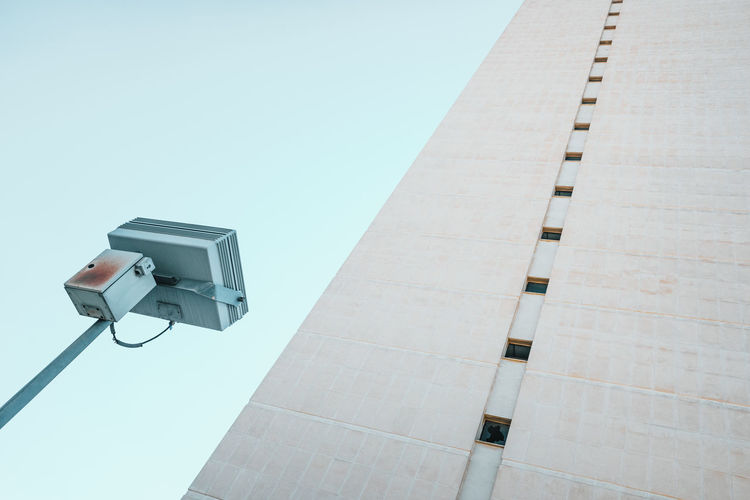 Low angle view of telephone pole against building against clear sky