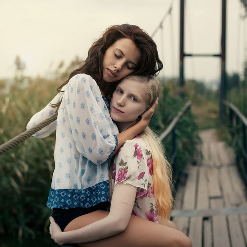 two young beautiful girls are walking in nature on a sunset background Love Bonding Casual Clothing Child Childhood Daughter Family Family With One Child Females Focus On Foreground Girls Hair Hairstyle Innocence Leisure Activity Lesbian Love Mother Outdoors Parent Positive Emotion Real People Three Quarter Length Togetherness Women The Portraitist - 2018 EyeEm Awards