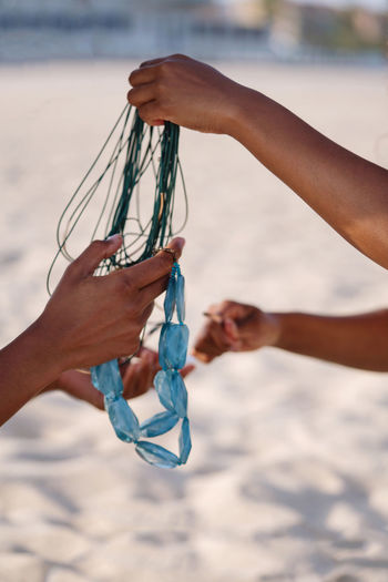 Two women at the beach holding tangled necklace