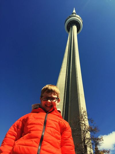 Low angle portrait of boy standing against tower and clear blue sky during sunny day