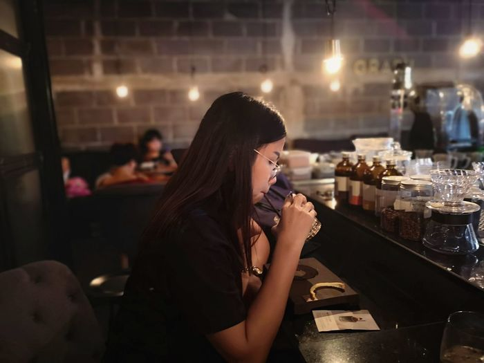 Side view of young woman sitting at restaurant