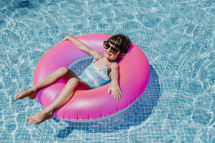 High angle portrait of smiling relaxing on inflatable ring in swimming pool