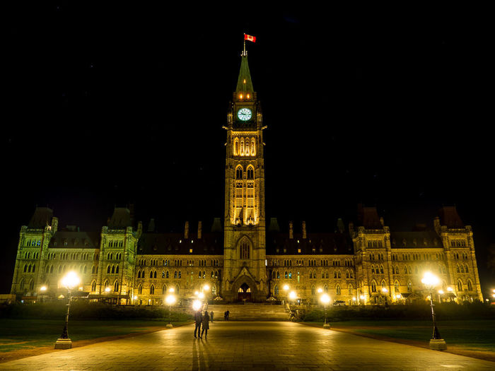 The Centre Block and the Peace Tower on the Parliament Hill, Ottawa, Canada in the evening Architecture Built Structure Building Exterior Sky Building Night Illuminated Tower Clock Tower City Travel Destinations Tall - High Travel Tourism History The Past Government Low Angle View Clock Evening Government Politics And Government Politics Democracy Icon Landmark People Yellow Flower Flag Parliament Building