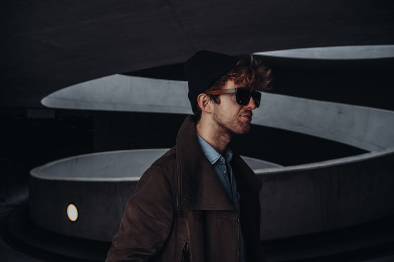 Young man wearing sunglasses in corridor