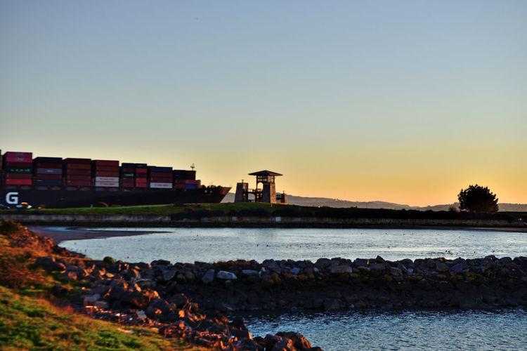 Sunset At Middle Harbor 1 Port Of Oakland,Ca. Maritime Middle Harbor Estuary Cove Lowtide  Jetty Mudflats Shoreline Park Observation Tower Sunset Silhouettes Sundown Sunset Sunset Collection Marin Headlands Freighter Freighter Enroute To San Francisco Bay Landscape_Collection Tree Knoll Rock-lined Shore Water Clear Sky Silhouette Reflection Harbor Calm Container Ship Shipyard