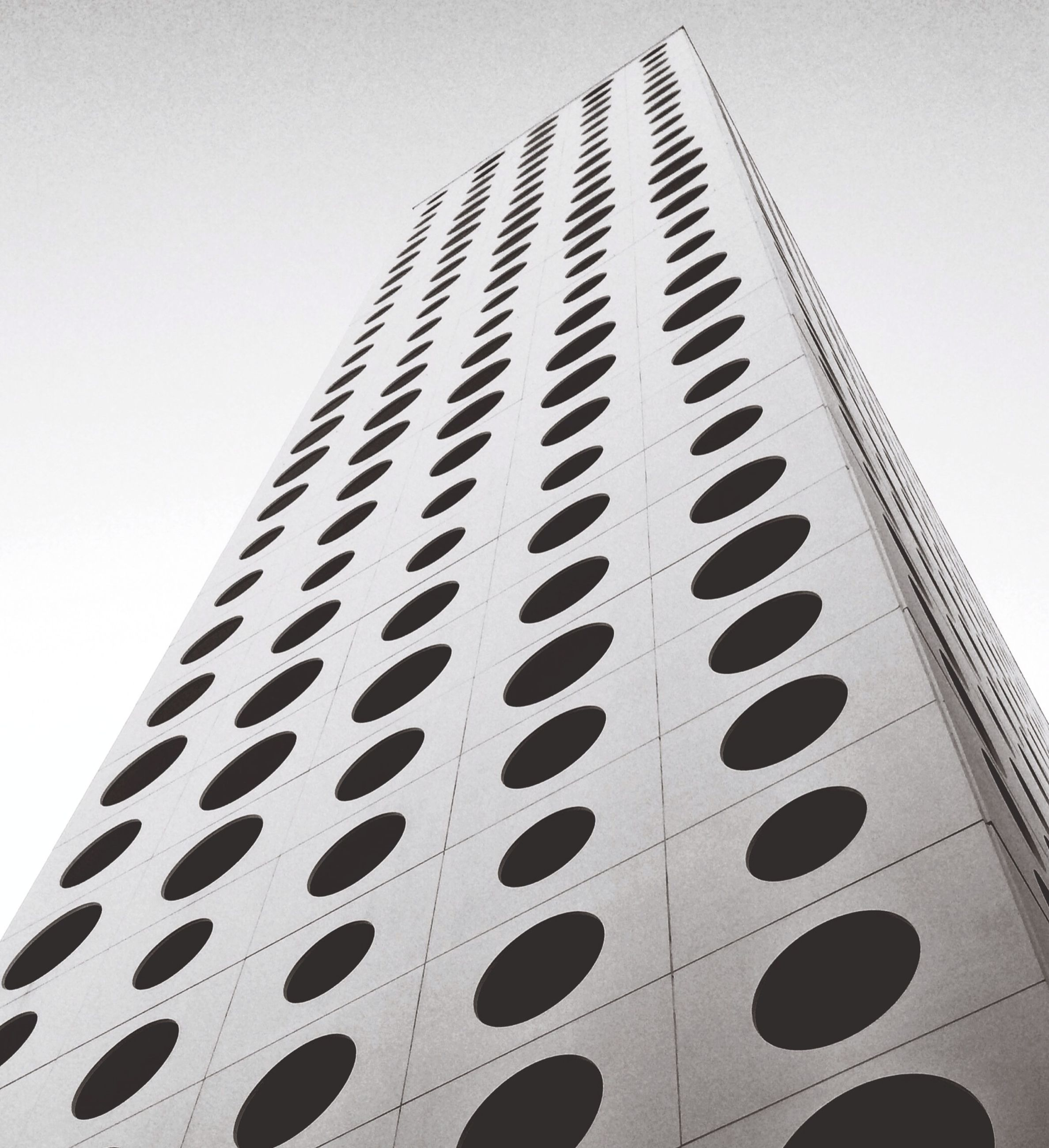 low angle view, architecture, built structure, building exterior, clear sky, building, tall - high, modern, office building, tower, sky, city, skyscraper, pattern, window, day, no people, outdoors, tall, directly below