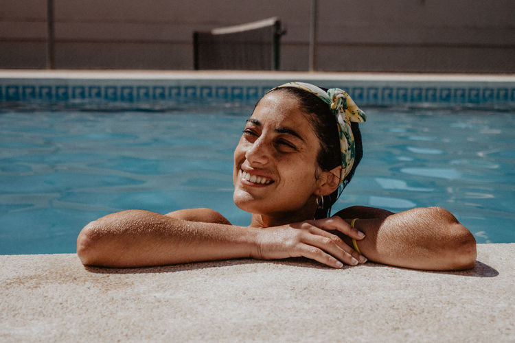 Close-up of woman smiling while looking away in swimming pool