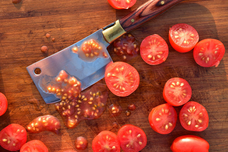 Overhead view flat lay of cut halves of grape tomatoes on wood cutting board with small cleaver
