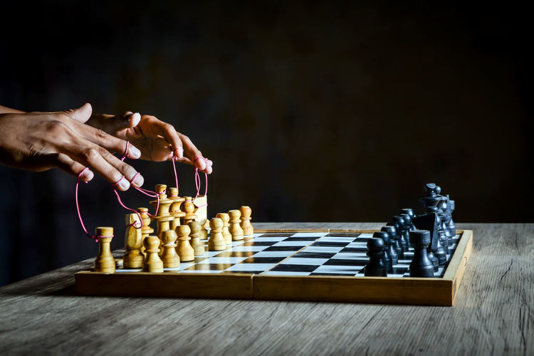 Man playing with chess against black background