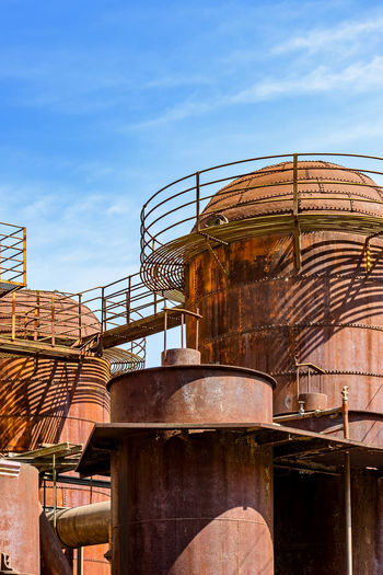 Low angle view of rusty metal structure against sky