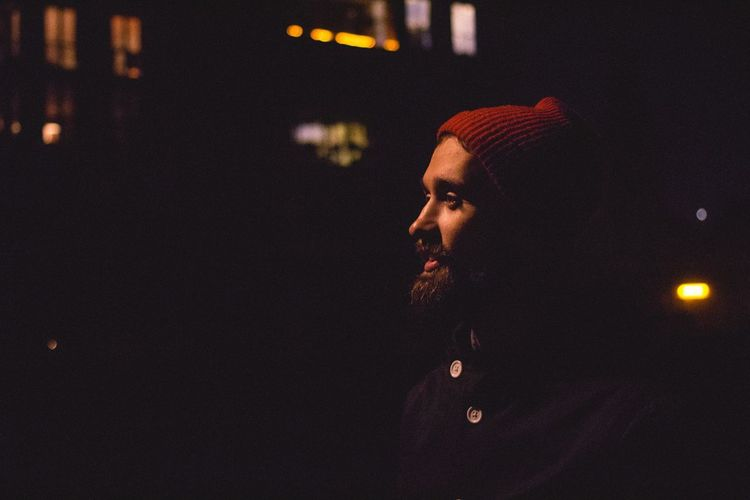 Bearded man wearing red knit hat at night