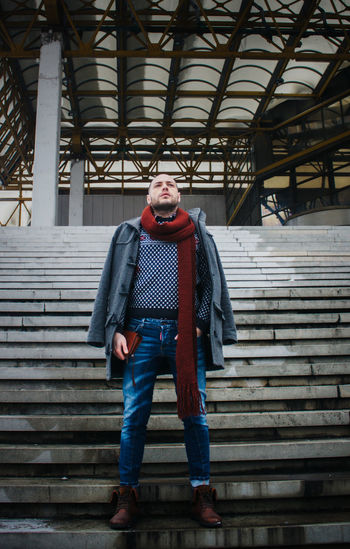 Man wearing warm clothing standing on steps outdoors