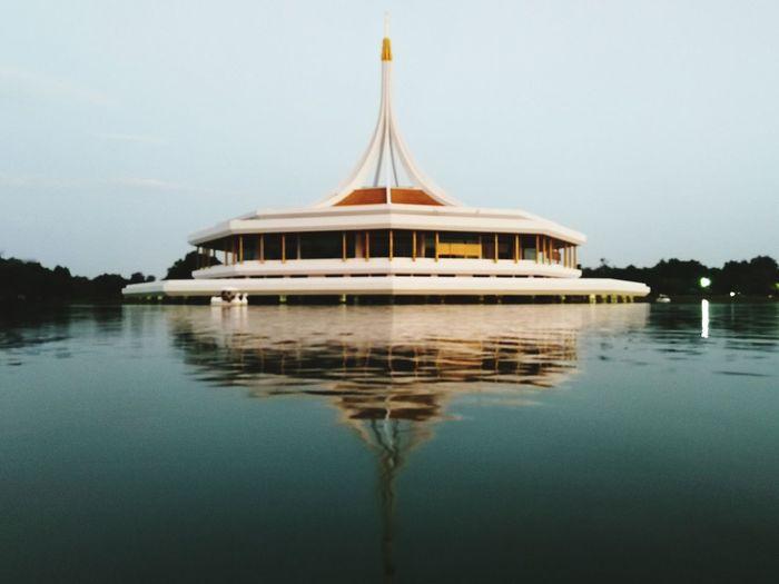 Pavilion reflecting on calm lake at suan luang rama ix