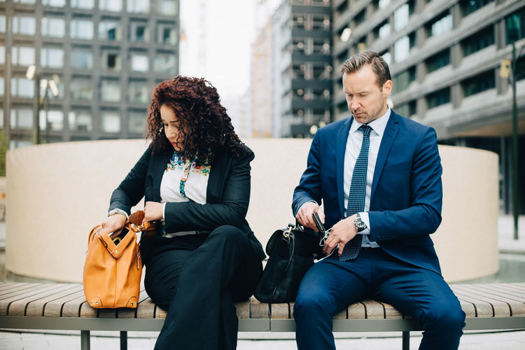 Young couple sitting in front of office building