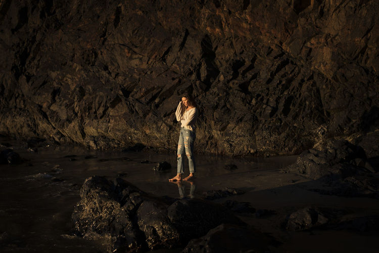 Woman standing on rock at shore