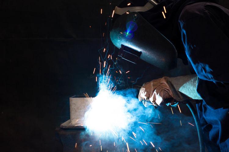 Man welding metal at factory