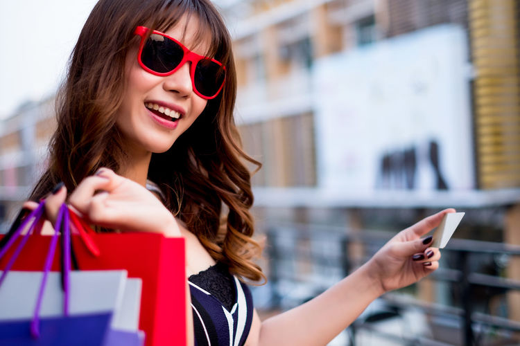Close-Up Of Young Woman Holding Shopping Bags In City
