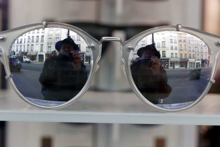 Mature man reflecting on sunglasses while photographing on city street